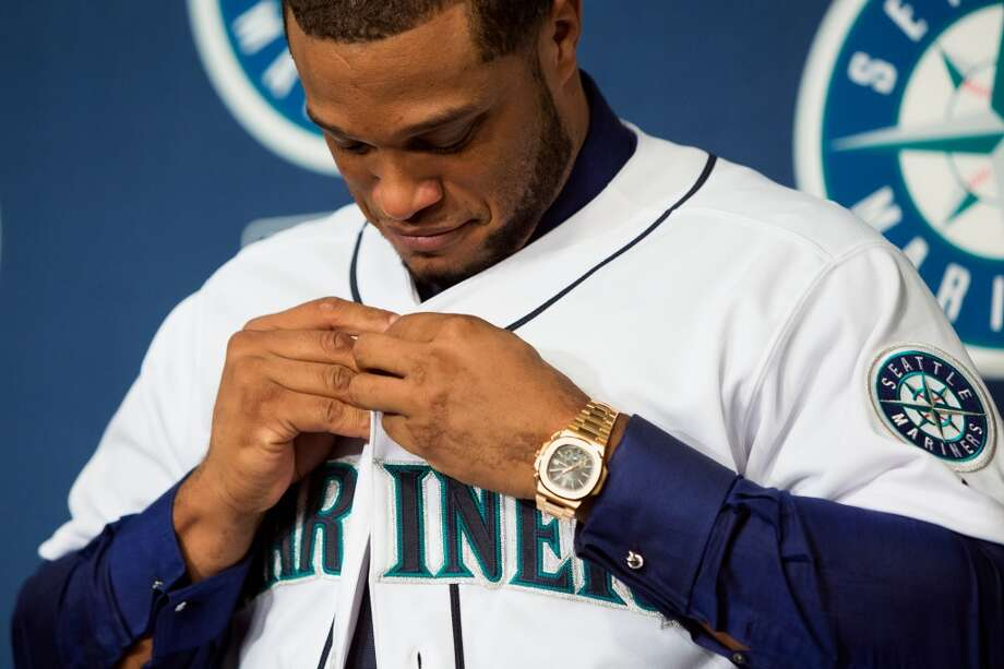 New Mariners second baseman Robinson Cano dons his jersey while being introduced to media Thursday, Dec. 12, 2013, at Safeco Field in Seattle. Cano is the biggest free-agent signing in the team's history. (Jordan Stead, seattlepi.com) Photo: JORDAN STEAD, SEATTLEPI.COM