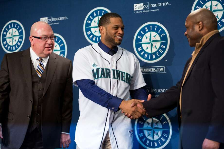 New Mariners second baseman Robinson Cano, center, shakes hands with Mariners manager Lloyd  McClendon Thursday, Dec. 12, 2013, at Safeco Field in Seattle. Cano is the biggest free-agent signing in the team's history. (Jordan Stead, seattlepi.com) Photo: JORDAN STEAD, SEATTLEPI.COM