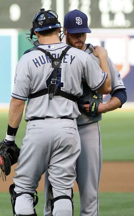 San Diego Padres catcher Nick Hundley, left, talks to pitcher Anthony Bass during the first inning of a baseball game against the Oakland Athletics in Oakland, Calif., Friday, June 15, 2012. (AP Photo/George Nikitin) Photo: George Nikitin, FRE / FR57659 AP