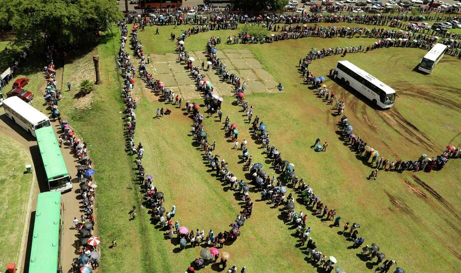 People queue to catch a bus to see the remains of Nelson Mandela at the Union Buildings in Pretoria, South Africa, on Thursday. Viewing will end Friday and the body will be transported to his home village, with burial on Sunday. Photo: Themba Hadebe, STF / AP