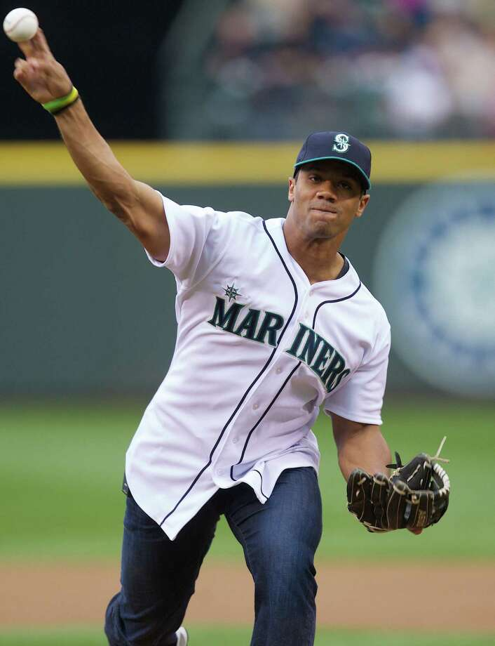 Seahawks quarterback Russell Wilson, throwing out the first pitch at a Mariners game, hit .229 with five homers and 26 RBIs over two Class A seasons. Photo: Stephen Brashear / Associated Press / FR159797 AP