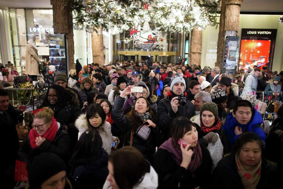 It's selfie time for one shopper as a crowd pours into the Macy's Herald Square flagship store in New York late last month. Photo: John Minchillo, FRE / FR170537 AP