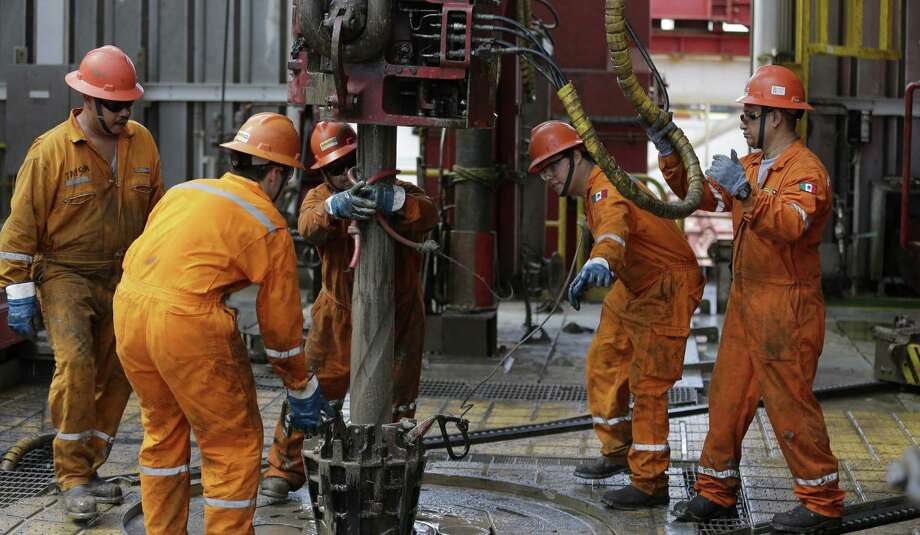 Oil workers lower the drill from the Centenario deep-water drilling platform off the coast of Veracruz in the Gulf of Mexico. Legislation passed by Mexico's Congress could open its oil industry to private investment. Photo: Dario Lopez-Mills / Associated Press / AP
