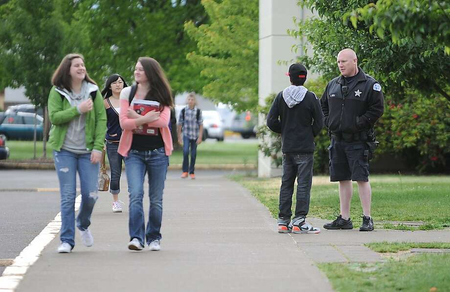 Albany police school resource officer Curtis Bell talks with a student while greeting teenagers as they arrive  at West Albany High School, Tuesday, May 28, 2013. One of their classmates,  a 17-year-old junior, was arrested late last week and charged with plotting to blow up the school. (AP Photo/Albany Democrat-Herald, Mark Ylen) Photo: Mark Ylen, Associated Press