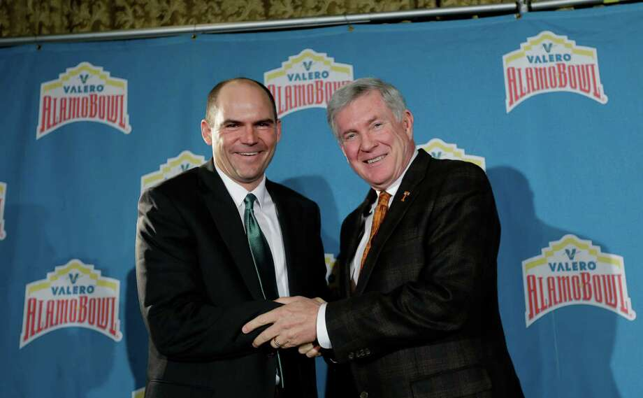Oregon coach Mark Helfrich, left, and Texas coach Mack Brown, right, pose for a photo following a Valero Alamo Bowl news conference, Thursday,  Dec. 12, 2013, in San Antonio. Texas and Oregon will play in the NCAA college football game Dec. 30. (AP Photo/Eric Gay) Photo: Eric Gay, STF / AP