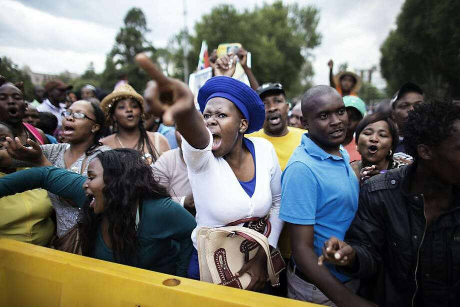 TOPSHOTS A South African woman reacts at the news that the time is over to visit the remains of former South African President Nelson Mandela at the Union Buildings on December 12, 2013 in Pretoria. Nelson Mandela was reclaimed by ordinary South Africans who queued in huge numbers in the hot sun Thursday to file past his open casket on a day reserved for the public. Mandela, the revered icon of the anti-apartheid struggle in South Africa and one of the towering political figures of the 20th century, died in Johannesburg on December 5 at age 95.  AFP PHOTO / MARCO LONGARIMARCO LONGARI/AFP/Getty Images Photo: Marco Longari, AFP/Getty Images