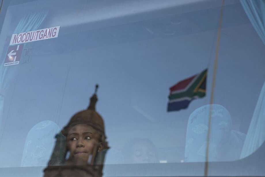 PRETORIA, SOUTH AFRICA - DECEMBER 12: A woman looks out from a coach outside the Union Buildings after viewing the body of anti-apartheid hero, former South African president Nelson Mandela, who is laying in state for three days, on December 12, 2013 in Pretoria, South Africa. Over 60 heads of state have travelled to South Africa to attend a week of events commemorating the life of former South African President Nelson Mandela. Mr Mandela passed away on the evening of December 5, 2013 at his home in Houghton at the age of 95. Mandela became South Africa's first black president in 1994 after spending 27 years in jail for his activism against apartheid in a racially-divided South Africa. (Photo by Oli Scarff/Getty Images) *** BESTPIX *** Photo: Oli Scarff, Getty Images
