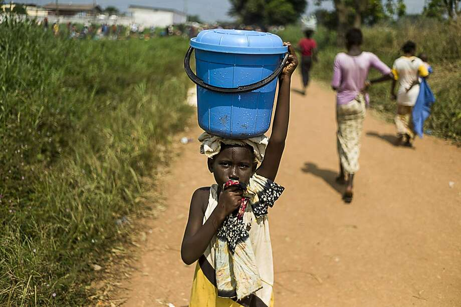 TOPSHOTS A young girl carries water at an internally displaced person camp (IDP) near the airport of Bangui on December 12, 2013 as aid officials fear that epidemics could spread easily and UN aid agencies have not delivered any food supplies to the camp for the last week. The medical charity Doctors Without Borders (MSF) has set up a mobile clinic capable of carrying out up to 300 consultations a day. Sectarian violence that claimed at least 400 lives in Bangui last week had abated following the weekend arrival of a 1,600-strong French intervention force, but many were still afraid to return to their homes. The Muslim-majority PK district in downtown Bangui was largely empty, with most residents having fled their homes to escape reprisal attacks by Christian vigilante groups.      AFP PHOTO / FRED DUFOURFRED DUFOUR/AFP/Getty Images Photo: Fred Dufour, AFP/Getty Images
