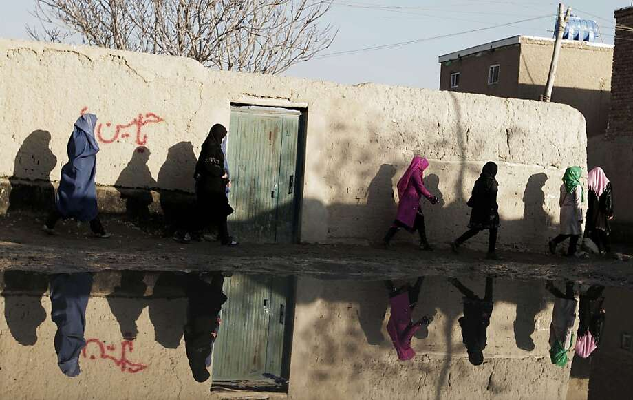 Afghan women walk near still water in Kabul, Afghanistan, Thursday, Dec. 12, 2013. Heavy rain flooded some streets in Kabul due to poorly designed sewage facilities. (AP Photo/Rahmat Gul) Photo: Rahmat Gul, Associated Press