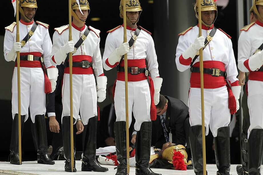 Soldiers of the Presidential Guard Battalion stand at attention as a fellow guard member is tended to after fainting while waiting for the arrival of visiting French President Francois Hollande at the Planalto presidential palace, in Brasilia, Brazil, Thursday, Dec. 12, 2013. Hollande is on a two-day visit to Brazil. (AP Photo/Eraldo Peres) Photo: Eraldo Peres, Associated Press