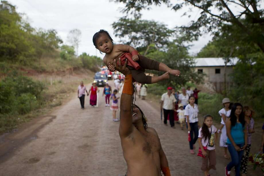 "How's the view up there? A man lifts his daughter over his head during a procession in honor of the Virgin of Guadalupe in Condega, Nicaragua. The Virgin of Guadalupe, also known as the ""Patroness of the Americas"" is celebrated during her feast day, Dec. 12, in many countries of Latin America. Photo: Esteban Felix, Associated Press"
