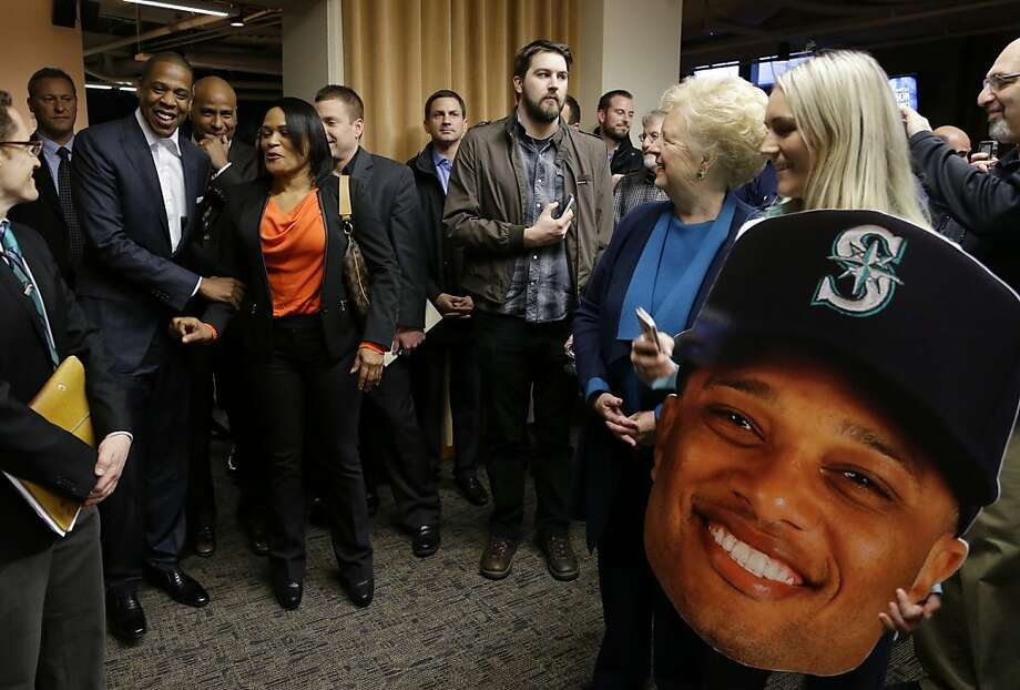 Rap artist Jay Z, left, one of the founders of Roc Nation Sports, stands with Robinson Cano's mother Claribel Mercedes, second from left as fans look on at right during an event honoring Cano as the newest member of the Seattle Mariners baseball team, Thursday, Dec. 12, 2013, in Seattle. (AP Photo/Ted S. Warren) Photo: Ted S. Warren, Associated Press