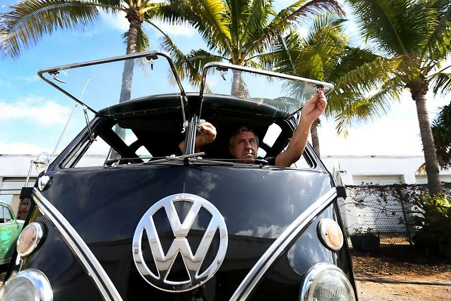 "POMPANO BEACH, FL - DECEMBER 12:  Bruce Wolczanski opens the window of a 1955 Volkswagen Oval-Window bus in the parking lot at his  McNab Foreign Car garage that specializes in restoring VW vehicles on December 12, 2013 in Pompano Beach, Florida. After 64 years, the German automaker announced it will finally stop producing the bus on December 20 in Brazil, the last country in the world to manufacture the van. Mr. Wolczanski said, 'he feels bad that the car will no longer be made, but it will live on as people drag them out of barns, fields and backyards and restore them'. He sees the buses continue to have a cult following with more and more young people buying and restoring the buses, ""they will never die"".  (Photo by Joe Raedle/Getty Images) Photo: Joe Raedle, Getty Images"