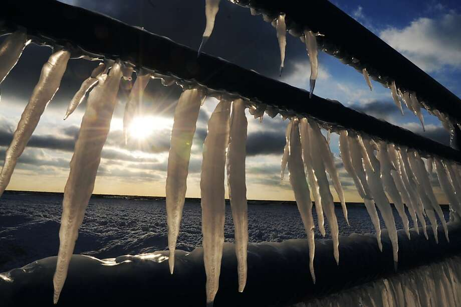 The sun breaks through a layer of clouds as icicles hang from railings along the south pier in St. Joseph, Mich., Thursday, Dec. 12, 2013. The National Weather Service says temperatures Thursday are well below freezing around the state. (AP Photo/The Herald-Palladium, Don Campbell) Photo: Don Campbell, Associated Press