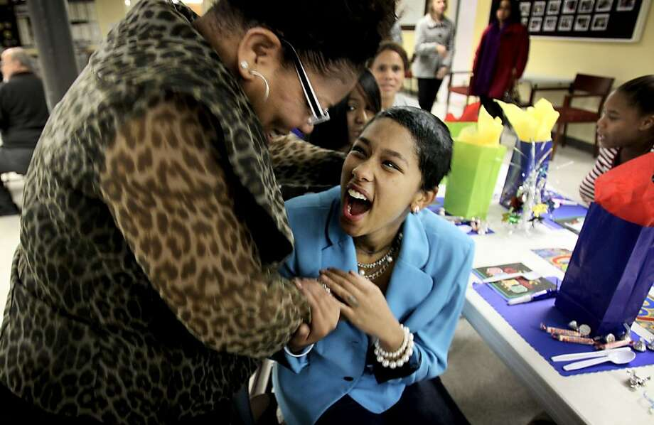 Kellie Johnson, 20, right, reacts when she hears that Janice Jones, left, has been helping keep a secret from her in Memphis, Tenn. Thursday, Dec. 12, 2013. Johnson learned that upon her graduation from the HopeWorks program that she is being hired for her very first job by Answering Advantage. Johnson came to the HopeWorks program after serving 22 months in prison for robbery to try to turn her life around and put it back on track.  (AP Photo/The Commercial Appeal, Mike Brown) Photo: Mike Brown, Associated Press