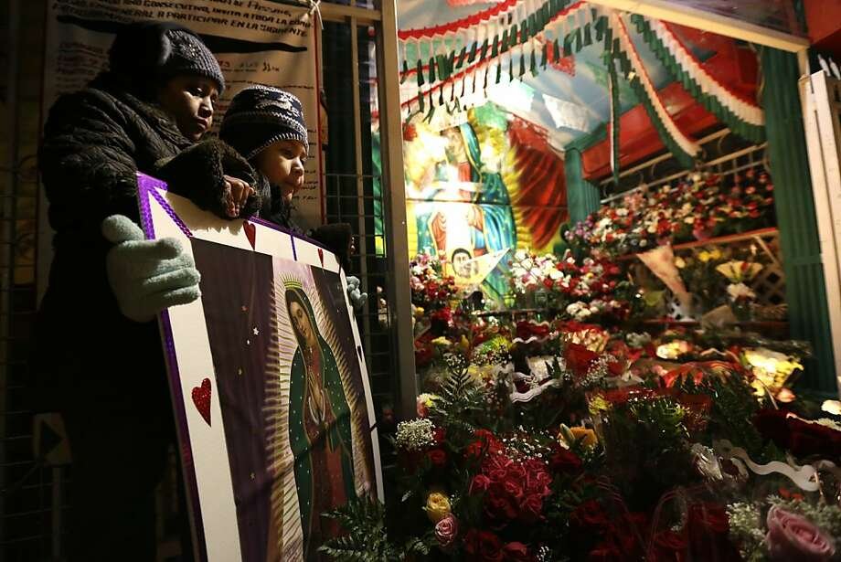 Susana Dorado, left, and her 6-year-old daughter, Evelin De La Luz stand behind a image of Virgin of Guadalupe while visiting a makeshift memorial where believers say an image of the virgin appeared on a tree stump in 2003, Thursday, Dec. 12, 2013, in Passaic, N.J. Catholic Mexicans living in New Jersey pay homage to the Virgin on Dec. 12, to observe what they believe was an apparition of the Virgin seen by Juan Diego, an indigenous man, on the hill of Tepeyac in Mexico City on Dec. 12, 1531.  (AP Photo/Julio Cortez) Photo: Julio Cortez, Associated Press