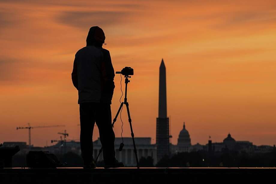 Yuan Ye photographs the sunrise over Washington, looking toward the Lincoln Memorial, Washington Monument and the Capitol, on a chilly winter day in the Nation's Capital, Thursday Dec. 12, 2013. (AP Photo/J.David Ake) Photo: J. David Ake, Associated Press