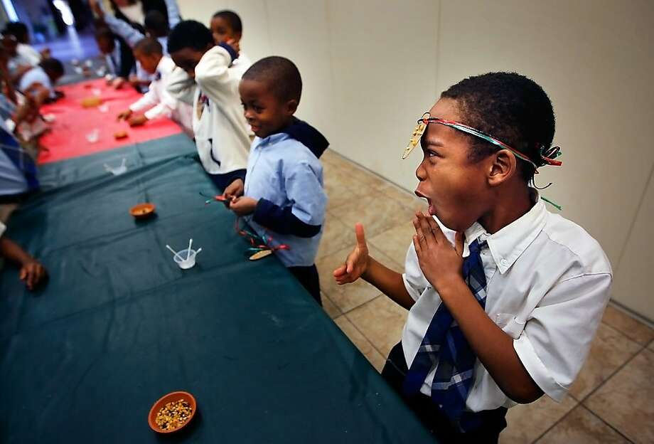 "Flying fists of fury: After donning a muhindi ""warrior"" medallion he made, Promise Academy second-grader Rantereon Rodgers demonstrates how he could karate-chop a table in two - if he wanted to - during a class about Kwanzaa at the Botanic Gardens in Memphis, Tenn. Photo: Jim Weber, Associated Press"