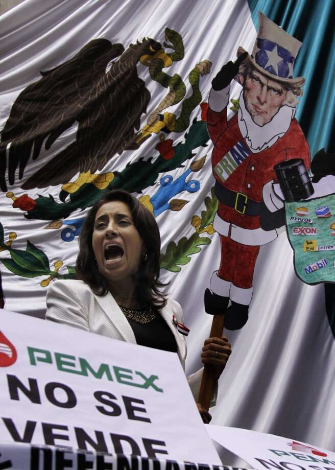 An opposition lawmaker shouts while holding a protest banner as dozens of leftist lawmakers take over the lower house trying to block discussion of the energy reform bill in Mexico City, Wednesday, Dec. 11, 2013. Photo: Marco Ugarte, Associated Press