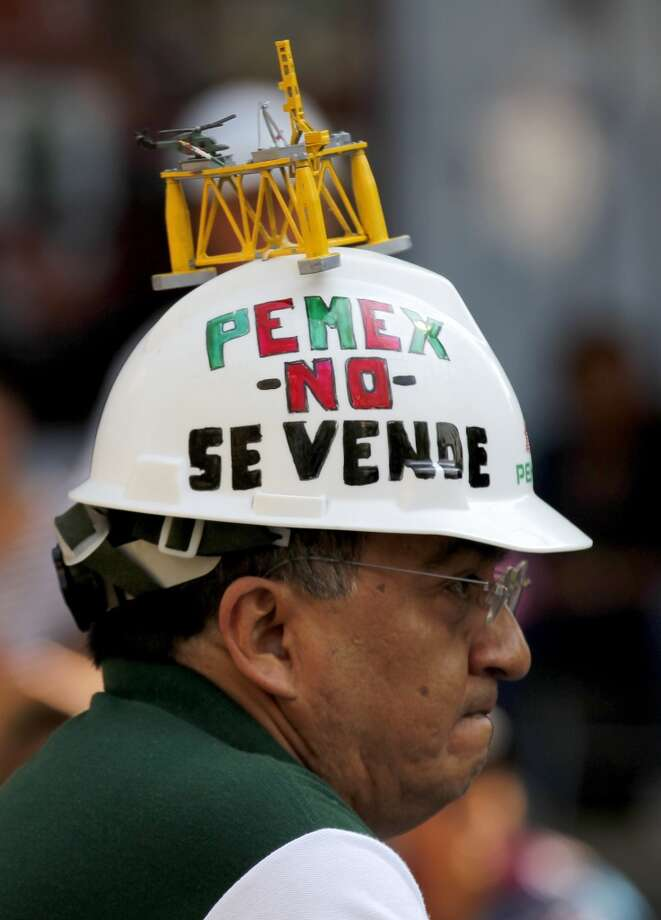 "A man wears a helmet with a miniature replica of the deep-water drilling platform and a message that reads in Spanish; ""Pemex is not for sale,"" during protests against a proposed energy reform bill, near the Senate building in Mexico City, Thursday, Dec. 5, 2013. Photo: Eduardo Verdugo, Associated Press"
