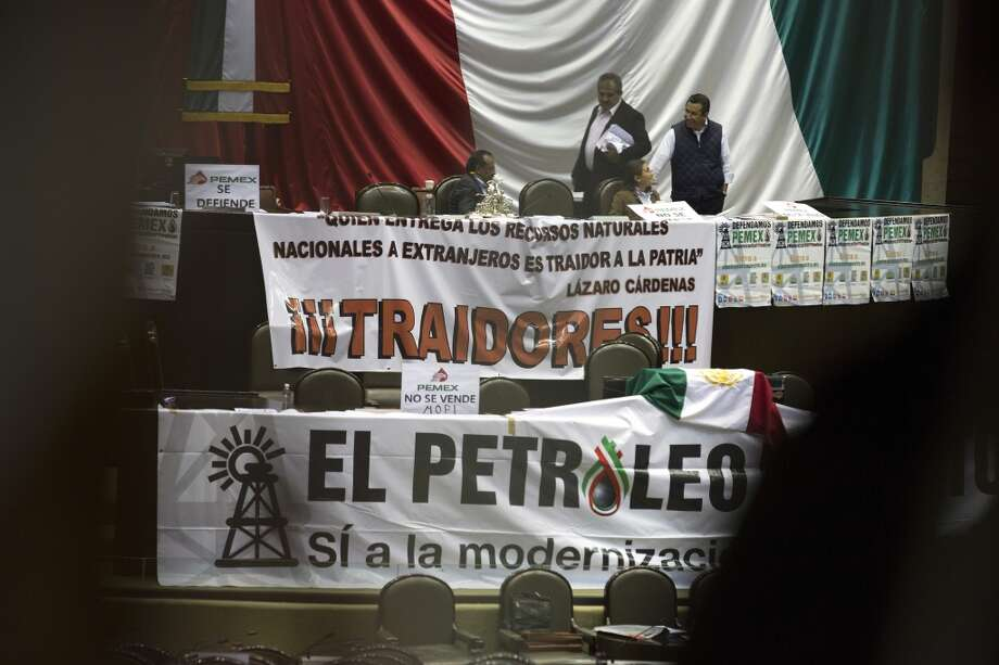 A banner with a slogan against proposed oil industry reforms (top) hangs above a banner with a slogan in support of the reform, at the Mexican Congress in Mexico City, Mexico, on Thursday, Dec. 12, 2013. Mexico's lower house passed an energy bill that ends Petroleos Mexicanos' 75-year oil monopoly in a bid to attract foreign investment and boost growth. Photo: Susana Gonzalez, Bloomberg
