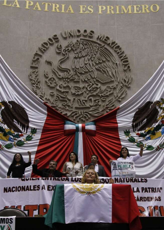 Opposition lawmakers occupy the podium at the National Congress in protest against the newly approved energy reform bill in Mexico City, Wednesday, Dec. 11, 2013. Photo: Marco Ugarte, Associated Press