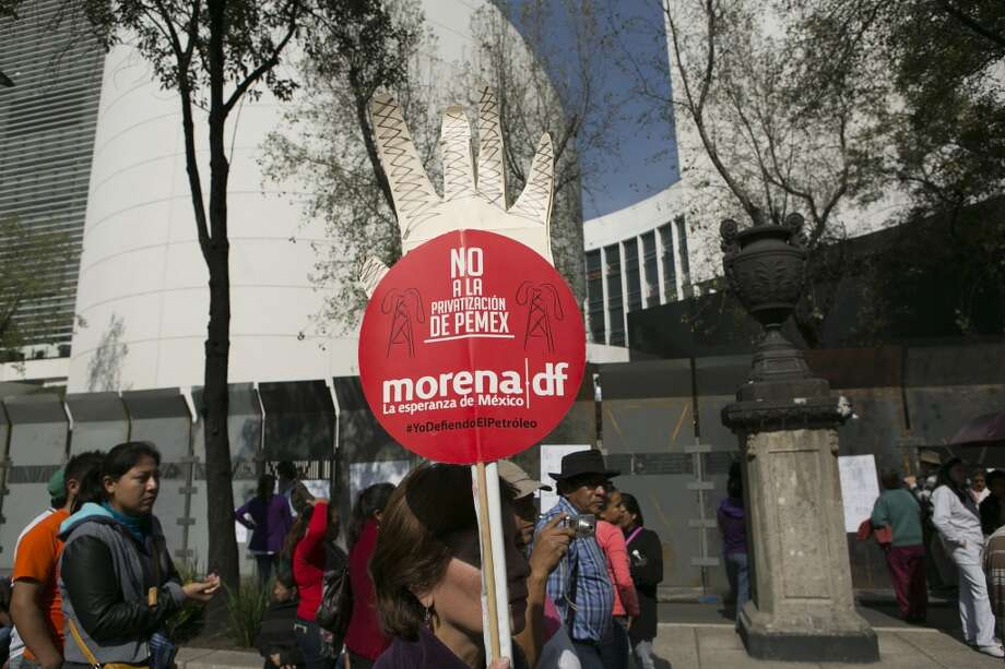 A National Regeneration Movement (MORENA) supporter holds a sign against privatizing Petroleos Mexicanos, or Pemex, during a demonstration outside the Mexican Senate in Mexico City, Mexico, on Wednesday, Dec. 4, 2013. Photo: Susana Gonzalez, Bloomberg