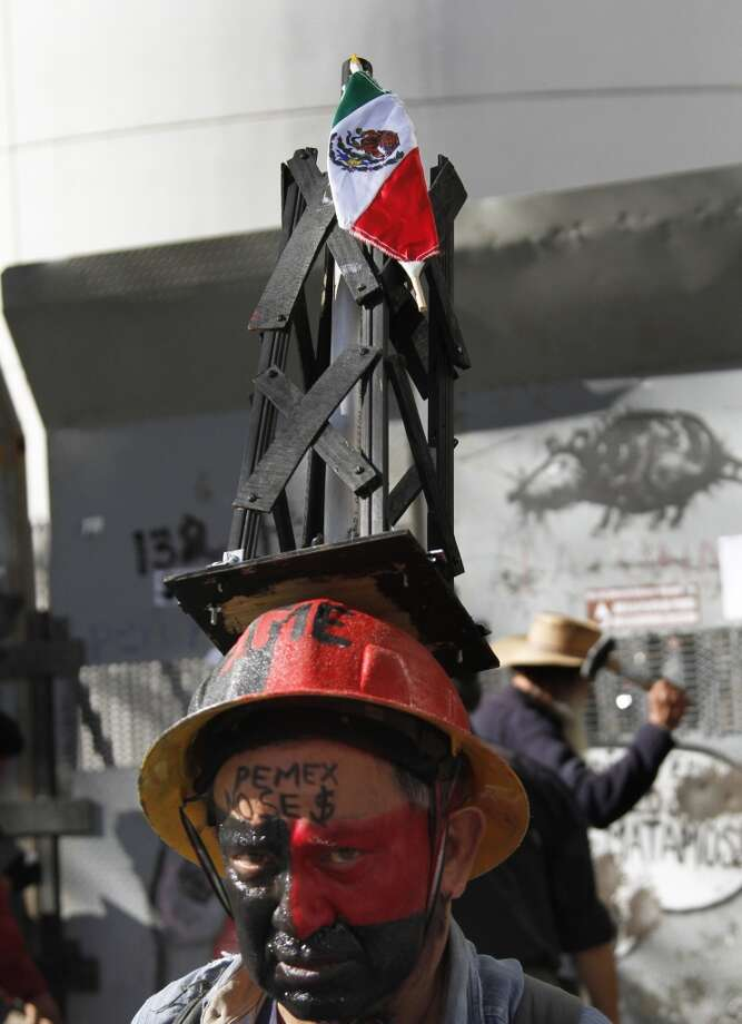 A protester wears a hat with a small oil well and a Mexican flag as he stands outside of the Senate building in Mexico City, Sunday, Dec. 8, 2013. Photo: Marco Ugarte, Associated Press