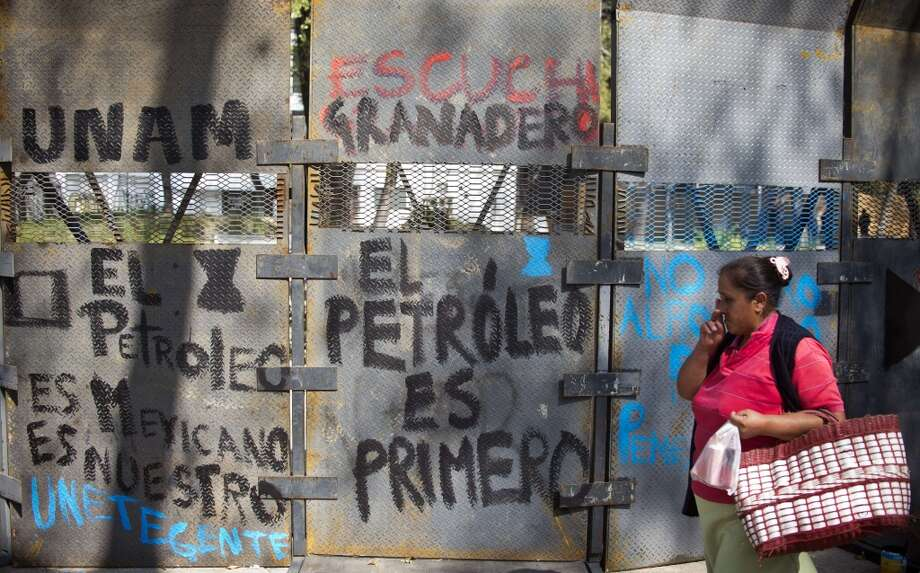 A woman walks next to a fence in front of the Mexican Senate on December 4 2013, in Mexico City, as supporters of Mexico's leftist leader Andres Manuel Lopez Obrador hold a rally against the privatization of the state-owned oil company Petroleos Mexicanos (Pemex). Lopez Obrador, who never recognized being defeated by Pena Nieto in the 2012 presidential election after claiming fraud, rejects Pena Nieto's plans to overhaul the tax system and open the country's state-controlled oil industry to foreign investors. Photo: RONALDO SCHEMIDT, AFP/Getty Images