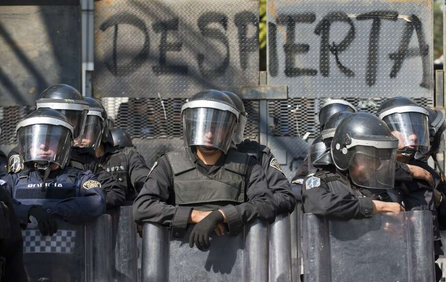 Mexican policemen stand guard next to a fence in front of the Mexican Senate on December 5 2013, in Mexico City, as supporters of Mexico's leftist leader Andres Manuel Lopez Obrador hold a rally against the privatization of the state-owned oil company Petroleos Mexicanos (Pemex). Lopez Obrador, who never recognized being defeated by Pena Nieto in the 2012 presidential elections, rejects Pena Nieto's plans to overhaul the tax system and open the country's state-controlled oil industry to foreign investors. Photo: RONALDO SCHEMIDT, AFP/Getty Images