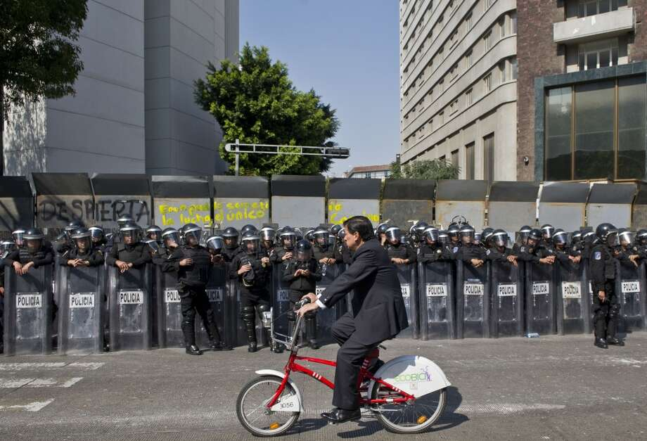 A man rides his bicycle in front of Mexican police officers in the Mexican Senate on December 5, 2013, in Mexico City, as supporters of Mexico's leftist leader Andres Manuel Lopez Obrador hold a rally against the privatization of the state-owned oil company Petroleos Mexicanos (Pemex). Lopez Obrador, who never recognized being defeated by Pena Nieto in the 2012 presidential elections, rejects Government's plans to overhaul the tax system and open the country's state-controlled oil industry to foreign investors. Photo: RONALDO SCHEMIDT, AFP/Getty Images