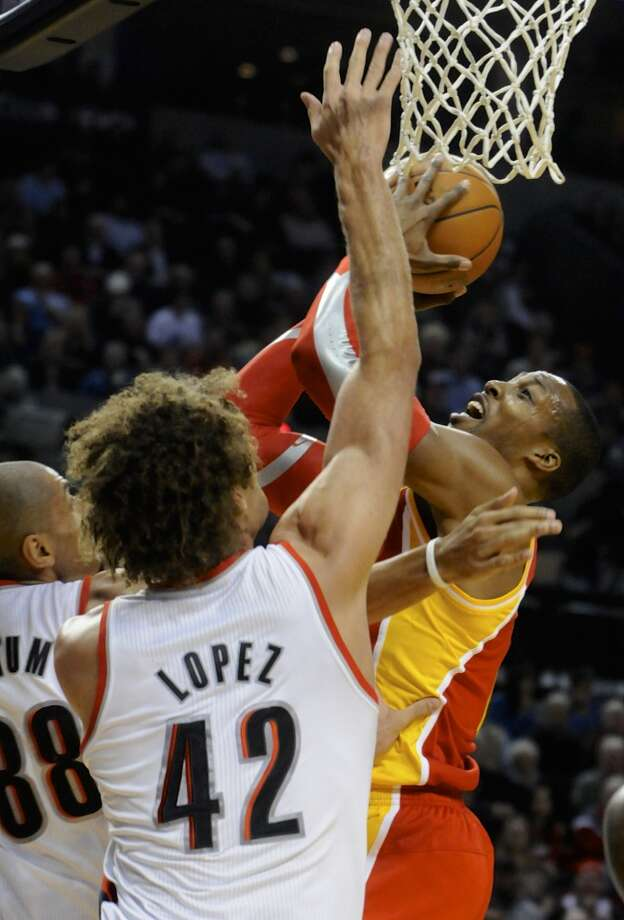 Dwight Howard, right, shoots against Robin Lopez (42) and Nicolas Batum (88). Photo: Greg Wahl-Stephens, Associated Press