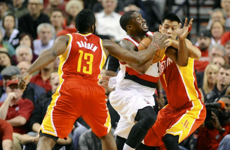 Rockets James Harden (13) and Jeremy Lin (7) defend a drive by Wesley Matthews (2). Photo: GREG WAHL-STEPHENS, Associated Press