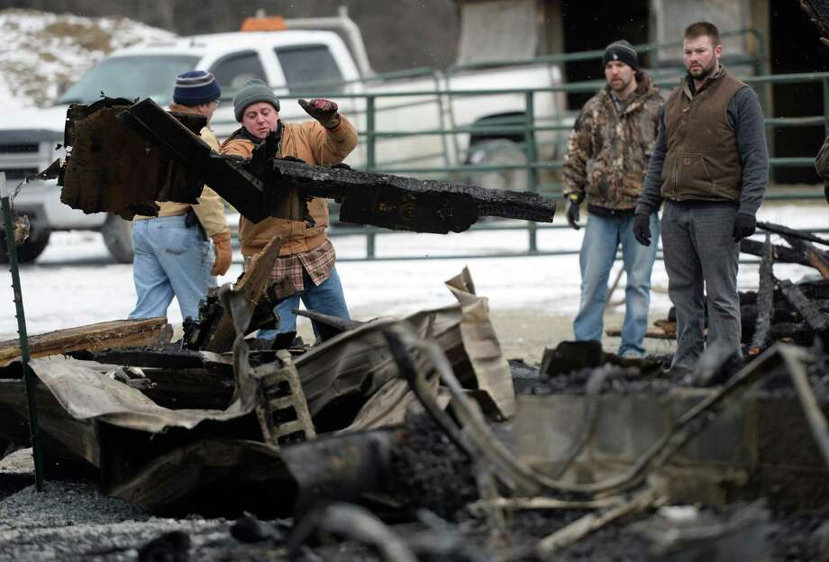 Terry Meissner, center, whose brother was lost in Thursday night?s tragic fire while trying to rescue horses from a burning barn, helps to clean up the fire scene Friday morning, Dec. 13, 2013, at 214 Thais Road in Averill Park, N.Y. One person and four horses were lost in the fire which started just before 8 p.m. near the intersection Delma Lane. (Skip Dickstein/Times Union) Photo: SKIP DICKSTEIN