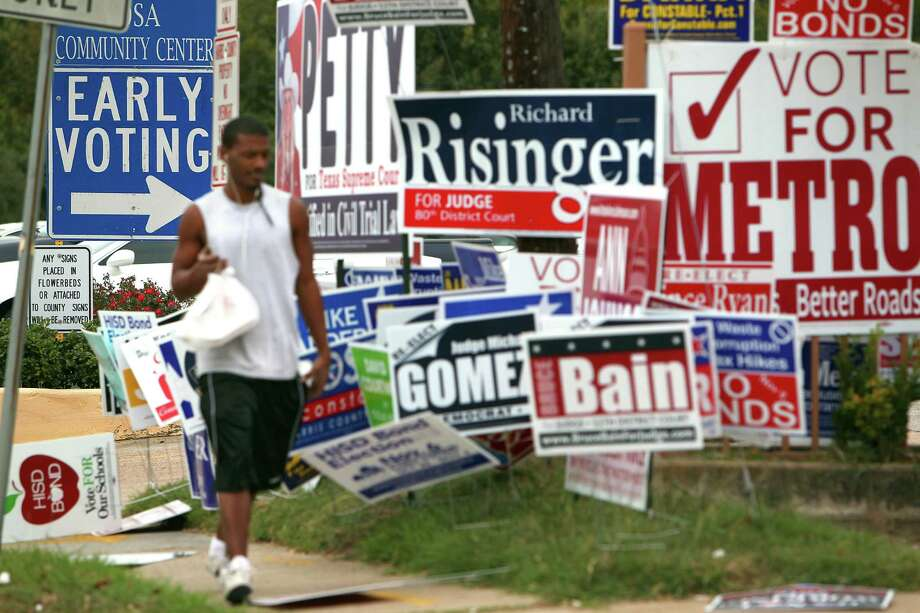 His lunch in hand, Zachary Brown walks past a group of campaign signs littering the area outside early voting at the Harris County Precinct 3 Trini Mendenhall Sosa Community Center Friday, Oct. 26, 2012, in Houston. 
