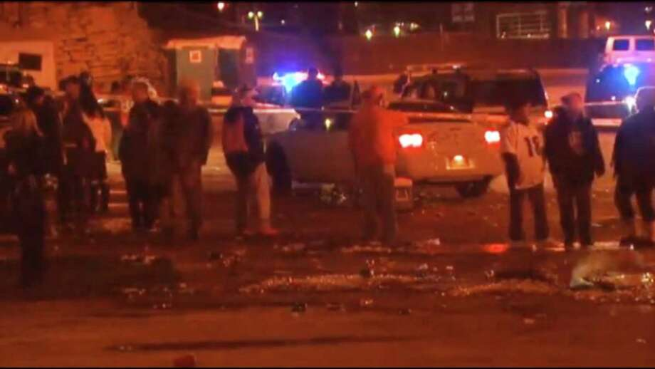 In this image from television provided courtesy of KMGH-THEDENVERCHANNEL.COM people mill around the area where at least three people were stabbed Thursday night Dec. 12, 2013 in a parking area at at Sports Authority Stadium Field at Mile High after the Denver Broncos' game.  DENVER OUT Photo: KMGH-The Denverchannel.com, AP / KMGH/The Denverchannel.com