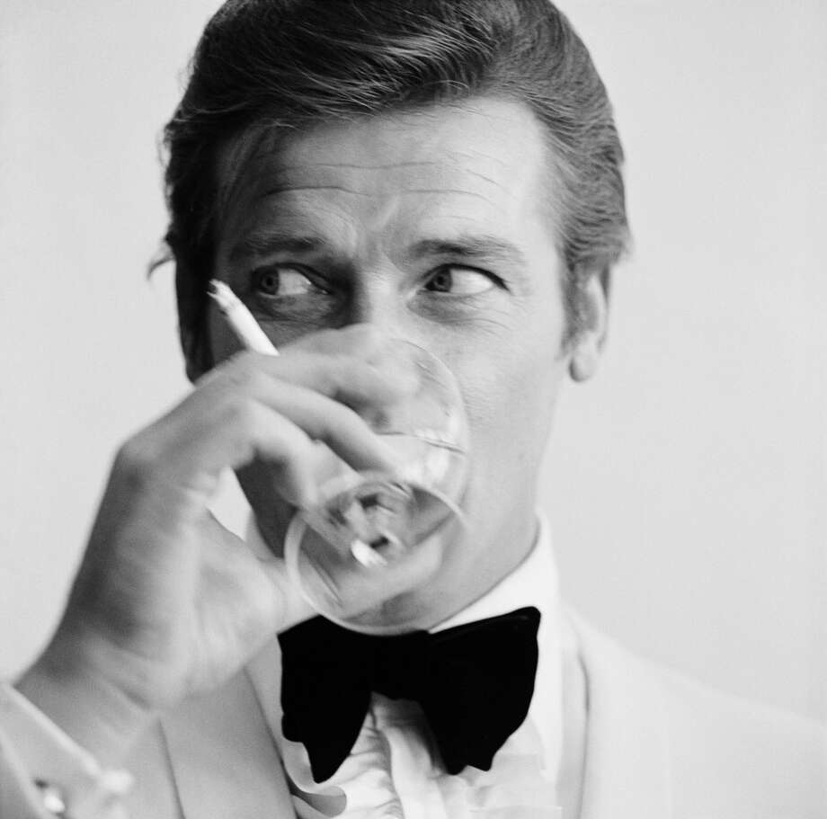 English film star Roger Moore, well known for his roles as James Bond and the Saint, downs a martini. Photo: Peter Ruck, Getty Images