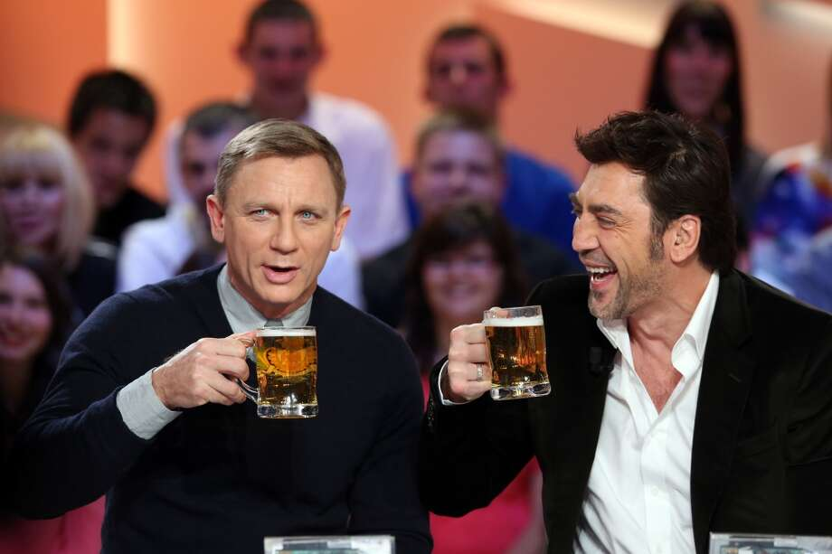 """British actor Daniel Craig (L) and Spanish actor Javier Bardem, starring in the new James Bond film """"Skyfall"""", toast with beer glasses as they take part in the TV show """"Le grand journal"""" on a set of French TV Canal+, on October 25, 2012 in Paris. Photo: AFP, AFP/Getty Images"""