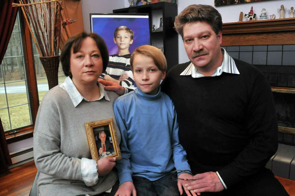 Oxsana Naumkin, left, and her husband Yuri, right, pose with their son, Peter, 10, and a photograph of their son Nicholas on Sunday, Dec. 8, 2013 in Saratoga Springs, NY. Nicholas was accidentally shot by a friend three years ago and then Oxsana's father died in an accident two weeks after Nicholas was killed. Oxsana holds a photograph of her father. (Paul Buckowski / Times Union)