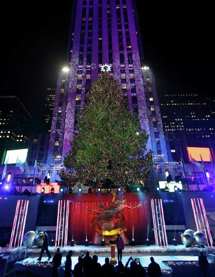 A young woman stands at a podium that was used to light the Rockefeller Center Christmas tree as others take photographs of the tree, Wednesday, Dec. 4, 2013, in New York. Some 45,000 energy efficient LED lights adorn the 76-foot tree. (AP Photo/Kathy Willens)  ORG XMIT: MER2013120423384195 Photo: Kathy Willens / AP