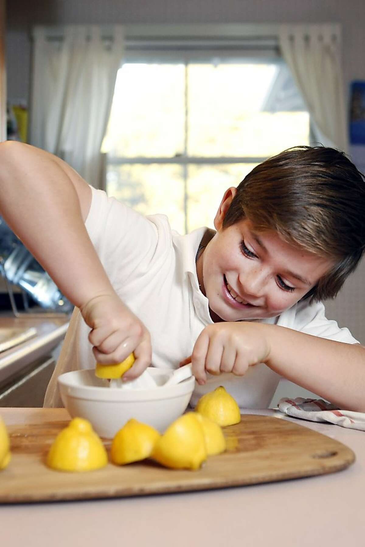Conall Lane, 8, who recently held lemonade sales to raise funds for local food banks, poses for a portrait while squeezing lemons in his home in Burlingame, CA, Thursday, December 12, 2013.