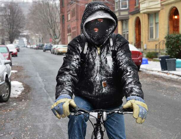 Joe Kehn of Troy rides his bicycle through a snow squall along Washington Street while riding to the market Friday, Dec. 13, 2013, in Troy, N.Y.  (John Carl D'Annibale / Times Union) Photo: John Carl D'Annibale