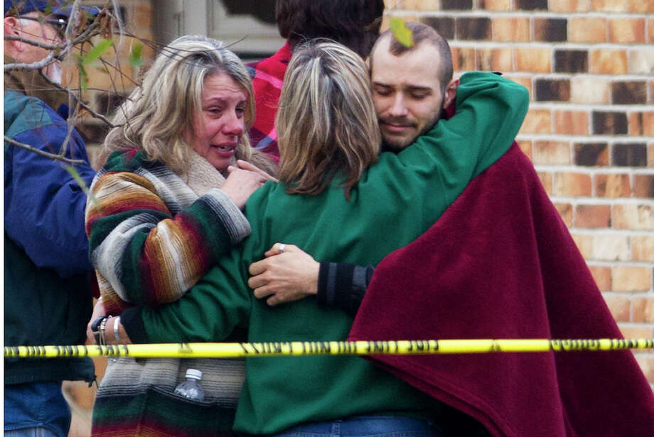 Family members gather at the scene of a fire in the 800 block of Clear Lake Road in Highlands in December. Caroline Stagner, 72, was found fatally stabbed in a burned home. See more scenes from the tragic case. Photo: Cody Duty, Houston Chronicle / © 2013 Houston Chronicle