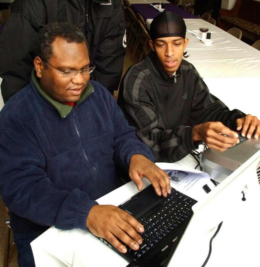 Troy Grant, seated left, and Shawn Brady  put finishing touches on  a media presentation for the 5th Annual Breakfast Honoring Dr. Martin Luther King at New Hope Baptist Church in Danbury in this 2007 File Photo Photo: Michael Duffy / The News-Times