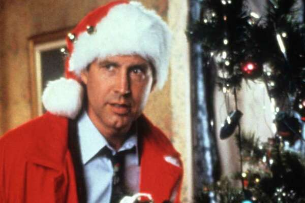 Chevy Chase hides behind the tree in a scene from the film 'Christmas Vacation', 1989.