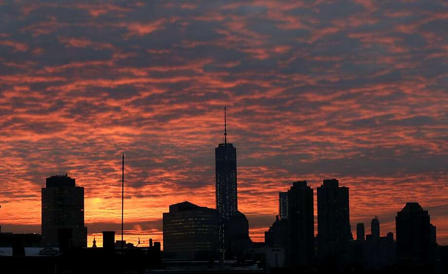 A rising sun illuminates a blanket of clouds behind the One World Trade Center as seen from The Heights neighborhood of Jersey City, N.J. New York was enjoying clear weather Friday, but snow was on the way. Photo: Julio Cortez, Associated Press