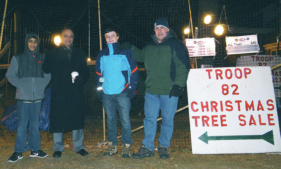 Boy Scout Troop 82 members and their dads stationed at the group's Christmas tree sale Thursday night adjacent to First Church Congregational: Jaimin Vyas, 12, and Amish Vyas, with Joe McKee, 14, and John McKee. Photo: Mike Lauterborn / Fairfield Citizen contributed