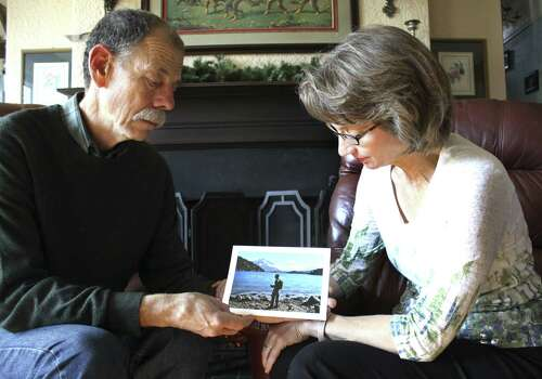 Mickey and Valerie Redus look at a photo of their son, Robert Cameron Redus, the University of the Incarnate Word student who was shot and killed by a campus police officer.  Photo: Albert Villegas / Baytown Sun / Baytown Sun