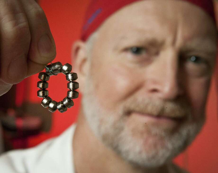 Dr. Patrick Reardon holds a LINX Reflux Management System, a tiny necklace of magnetic titanium beads that helps relieve symptoms of acid reflux. Photo: Nick De La Torre / Houston Chronicle / © 2013 Houston Chronicle