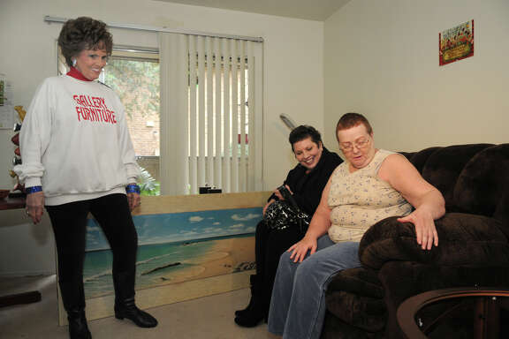 Karen Klaus, from right, of The Woodlands, with friend Kelly Quin, admires a new recliner delivered to her home by Georgia Ann Spears of Gallery Furniture. Klaus' is one of 30 households selected to receive furniture as part of Gallery Furniture's annual giveaway.